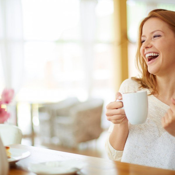 Image of young and pretty woman with cup of coffee laughing in cafe